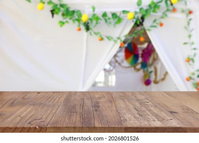 Jewish festival of Sukkot. Traditional succah (hut) with decorations. Empty wooden old table for product display and presentation. - Shutterstock ID 2026801526