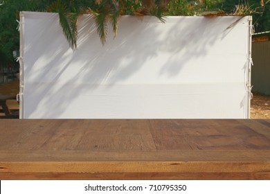 Jewish festival of Sukkot. Traditional succah (hut). Empty wooden old table for product display and presentation.