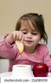 Jewish girl dipping apple slices into honey on Rosh HaShanah the Jewish New Year.