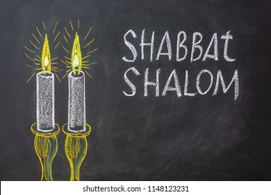 Jewish greetings Shabbat Shalom and candles painted on a chalkboard. May you dwell in completeness on this seventh day.