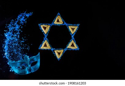 Jewish holiday background with hamantaschen cookies and carnival mask for Purim.