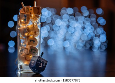 jewish holiday Chanukah/Hanukkah with wooden dreidels / sovivon (spinning top) in the glass over glitter shiny background