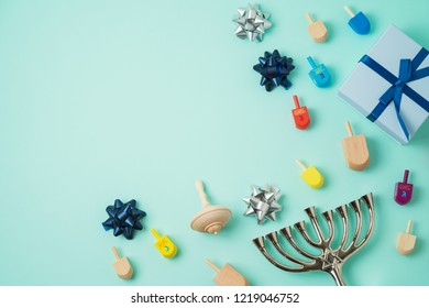 "Jewish holiday Hanukkah background with menorah,  gift box and spinning top. Top view from above. Flat lay. Hebrew letters  "" Great miracle happened here"""