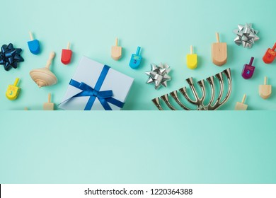 "Jewish holiday Hanukkah background with menorah,  gift box and spinning top. Top view from above. Flat lay. Hebrew letters :""Great miracle happened here"""