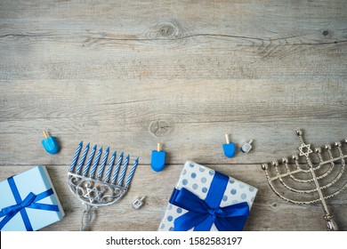 Jewish holiday Hanukkah background with menorah, gift boxes and dreidel on wooden table. Top view from above