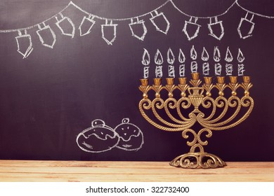 Jewish holiday Hanukkah background with menorah over chalkboard with hand sketched symbols