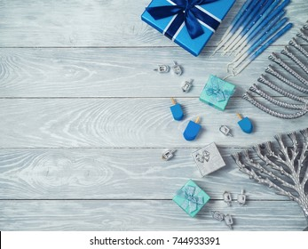Jewish holiday Hanukkah background with menorah, gift box and dreidel over wooden table. View from above. Flat lay