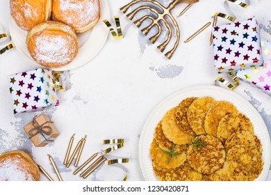 Jewish holiday Hanukkah background. Traditional dishes - sweet doughnuts and potato latkes. Hanukkah table setting on white background. Copy space