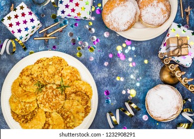 Jewish holiday Hanukkah background. Traditional dishes - sweet doughnuts and potato latkes. Hanukkah table setting on blue background. Copy space