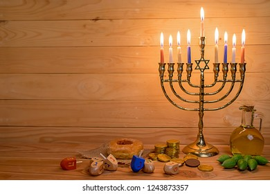 Jewish holiday hanukkah celebration with menorah (traditional candelabra), wooden dreidels (spinning top), donut, olive oil and chocolate coins on wooden table.