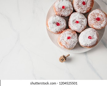 Jewish holiday Hanukkah concept and background. Hanukkah food doughnuts and traditional spinnig dreidl or dredel on white marble table background. Copy space for text. Shallow DOF.Top view or flat lay