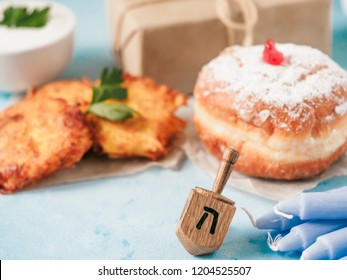 Jewish holiday Hanukkah concept and background. Hanukkah food doughnuts and potatoes pancakes latkes, giftbox, candle and traditional spinnig dreidl on blue background. Copy space for text.