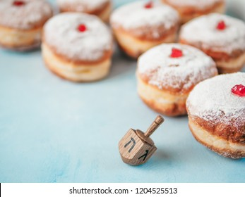 Jewish holiday Hanukkah concept and background. Hanukkah food doughnuts and traditional spinnig dreidl or dredel on blue background. Copy space for text. Shallow DOF