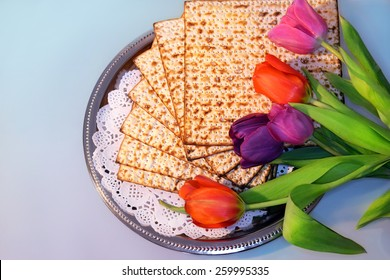 jewish holiday of Passover and its attributes, with matzo and spring tulips - Happy Passover