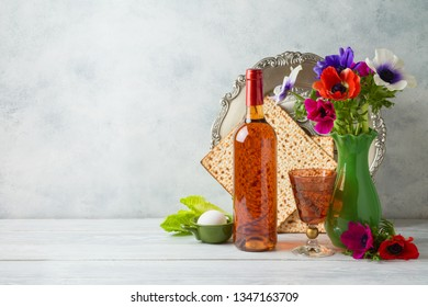 Jewish holiday Passover background with flowers, wine, matzo and seder plate on wooden table