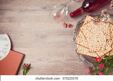 Jewish holiday Passover background with matzah, seder plate and wine. View from above