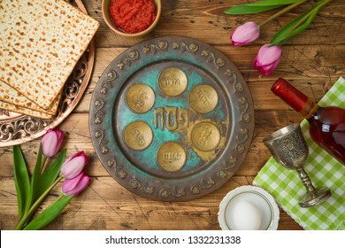 Jewish holiday Passover background with matzo, seder plate, wine and tulip flowers on wooden table. Top view from above.