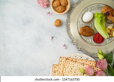 Jewish holiday Passover background with matzo, seder plate and spring flowers. Top view from above. Flat lay