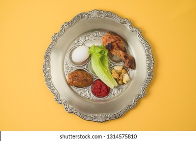Jewish holiday Passover celebration concept with traditional seder plate on yellow background. Top view from above.
