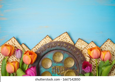 Jewish holiday Passover celebration concept with seder plate, matzah and tulip flowers on wooden table. Traditional Pesah plate text in Hebew : Passover. Top view from above.