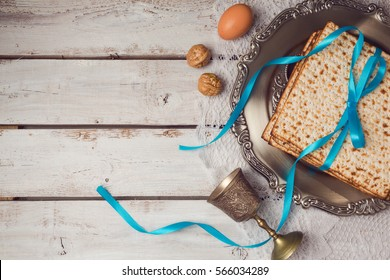Jewish holiday Passover concept with matzah, seder plate and wine glass on white table background. View from above. Flat lay