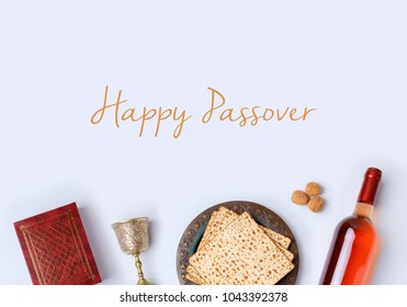 Jewish holiday Passover frame composition with wine, matzo and seder plate on white background. View from above. Flat lay