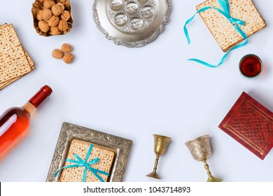 Jewish holiday Passover frame composition with wine, matzo and seder plate on white background. View from above. Flat lay. Hebrew Text:  horseradish, celery, egg, bone, bitter herb, fruit paste