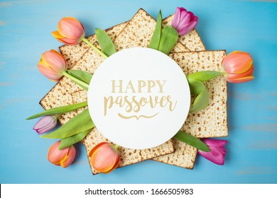 Jewish holiday Passover greeting card with matzah and tulip flowers on wooden table. Pesach background. Top view from above.
