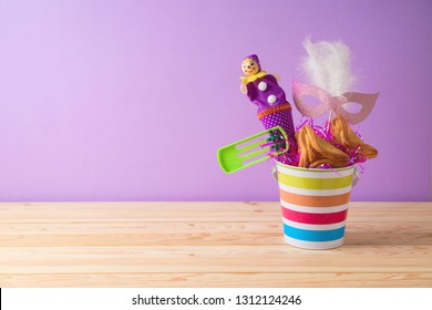 Jewish holiday Purim background with bucket, carnival mask, noisemaker and hamantaschen cookies on wooden table. Creative Purim basket idea
