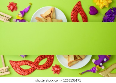 Jewish holiday Purim background with carnival mask and hamantaschen cookies. Top view from above. Flat lay