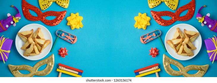 Jewish holiday Purim background with carnival mask, noisemaker and hamantaschen cookies. Banner design. Top view from above. Flat lay