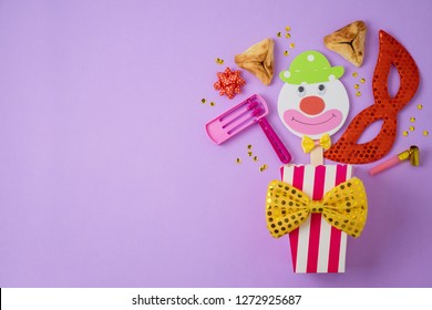 Jewish holiday Purim background with carnival mask, paper clown and hamantaschen cookies. Top view from above. Flat lay