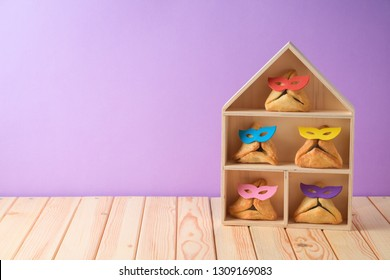 Jewish holiday Purim background with cute funny  hamantaschen cookies and toy house on wooden table. Creative Purim basket idea