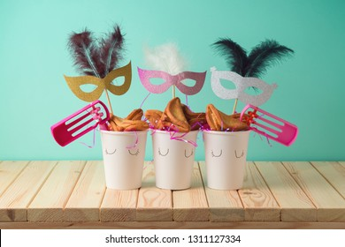 Jewish holiday Purim background with paper cup, carnival mask, noisemaker and hamantaschen cookies on wooden table. Creative Purim basket idea