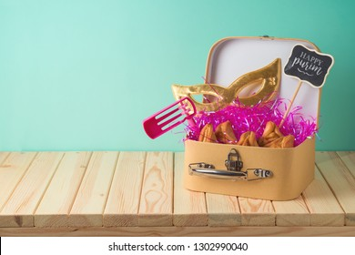 Jewish holiday Purim background with suitcase box, carnival mask, noisemaker and hamantaschen cookies on wooden table. Creative Purim basket idea
