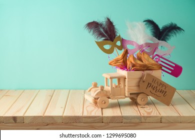 Jewish holiday Purim background with toy truck, carnival mask, noisemaker and hamantaschen cookies on wooden table. Creative Purim basket idea