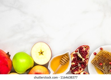 Jewish holiday Rosh Hashana background with honey, pomegranate and apples on white marble table. flat lay. top view with copy space