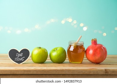 """Jewish holiday Rosh Hashana background with honey, apple and pomegranate on wooden table. Hebrew text """"Happy New Year"""""""