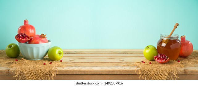 Jewish holiday Rosh Hashana background with honey, apple and pomegranate on wooden table
