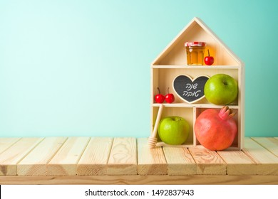 "Jewish holiday Rosh Hashana creative decor background with toy house, honey jar, apple and pomegranate on wooden table. Hebrew text ""Happy New Year"""