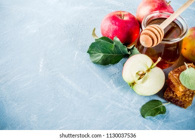 Jewish holiday Rosh Hashanah or apple feast day concept, with red apples, apple leaves and honey in jar, light blue background copy space above