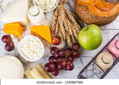 Jewish holiday Shavuot background. Milk, bread, fruits and dairy products on white table