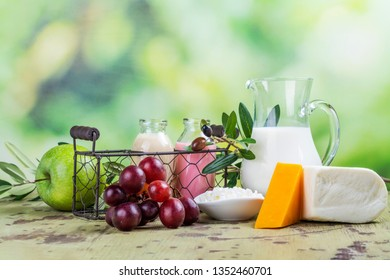 Jewish holiday Shavuot background. Milk, bread, fruits and dairy products on wooden table