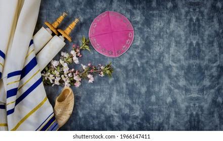Jewish holidays, during prayer items kippa with prayer shawl tallit on shofar, torah scroll in a synagogue