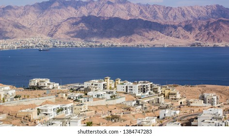 Jewish Israeli city Eilat aerial photography from above with view on a buildings on Red sea Gulf of Aqaba water surface and opposite Jordanian waterfront, Middle East place for summer vacation