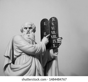 jewish Jehovah Statue of God with a book in their hands against on a white background. Biblical Ten Commandments inscribed on stone tablets