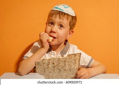 Jewish little child taking a bite from matzah. Israel Pessach illustration.