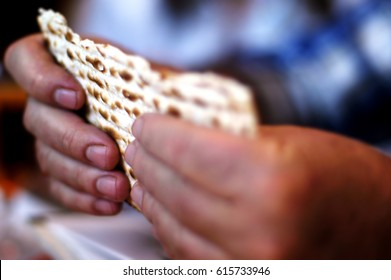 Jewish man is blessing on Matzah (unleavened bread) during blessings for the Jewish holiday of Passover Seder meal