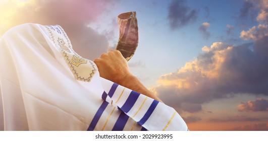 Jewish man blowing the Shofar (horn) of Rosh Hashanah (New Year). Religious symbol - Shutterstock ID 2029923995