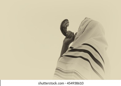 Jewish man blowing the Shofar (horn) of Rosh Hashanah (New Year). Religious symbol. Old style filter